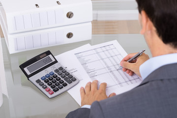 Male accountant calculating invoices