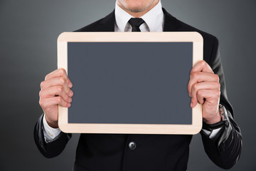 Midsection Of Businessman Holding Blank Slate
