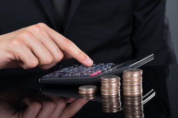 Businessman Using Calculator By Stacked Coins