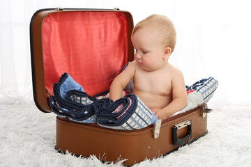 Cute baby boy sitting in suitcase in room
