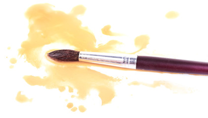 Brush and spilled paint isolated on white