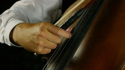 Cellist playing on cello. Musician in a darkened background.