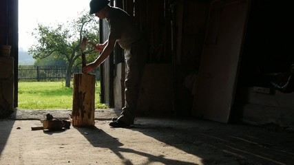 Man with axe chops wood in the shed