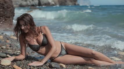Sexy girl in black bikini with rhinestones having fun lying on