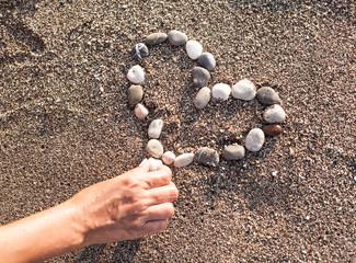 Woman's hand making heart of marine shingles on the sand.