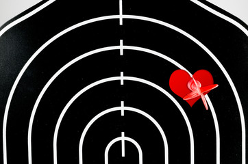 red arrow shooting at heart position of profile shape black dart