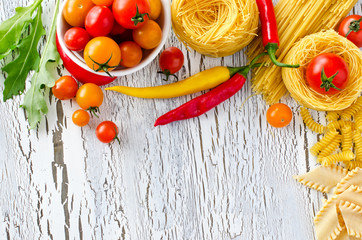 Mix of pasta, tomatoes and chili copy space wooden background