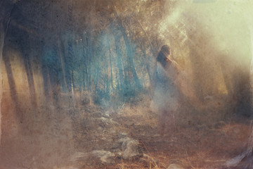 surreal blurred background of young woman stands in forest. abst