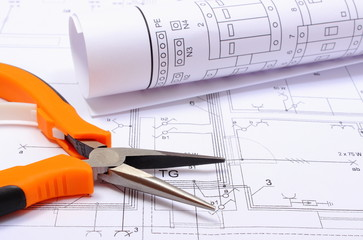 Pliers and rolled electrical diagram on construction drawing