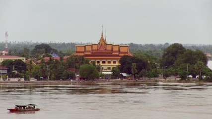 Small boat across the mekong river in front of the pagoda