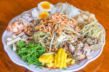papaya salad with horse crab , shrimp and  squid , wood backgrou