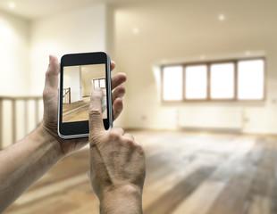 Smarthphone with man hand taking picture in modern loft studio