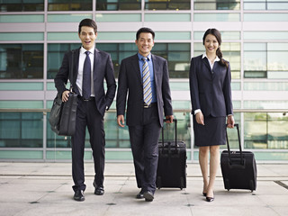 asian business team traveling with luggage