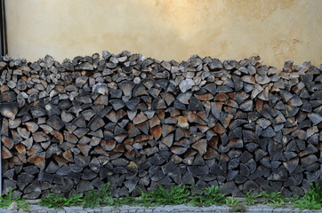 Background of dry chopped firewood logs in a pile  at the wall