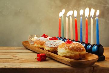 Menorah and donuts for Jewish holiday Hanukkah on wooden table