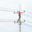 Electrician lineman repairman worker at climbing work on electri
