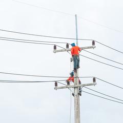 Electrician lineman repairman worker at climbing work on electri