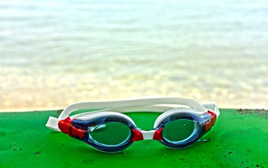 Blue and red goggles by the sea