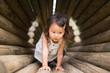 木のトンネルで遊ぶ少女