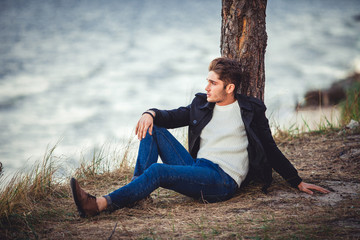 young man on sea background. autumn beach