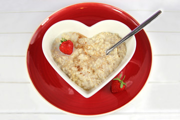 Breakfast of Oatmeal or Proodge in a heart bowl wit hstrawberry