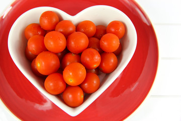 Cherry tomatoes in a heart shaped bowl on red plate