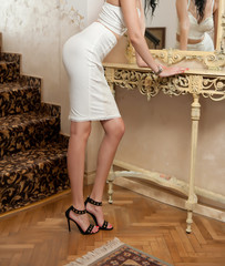Beautiful young woman in short white tight fit skirt and corset