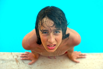 Young teenage boy looks up in swimming pool