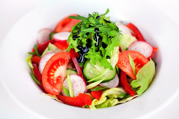 salad with tomato, cucumber, radish, arugula and balsamic