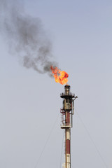 Fire from a gas torch, in a large oil refinery