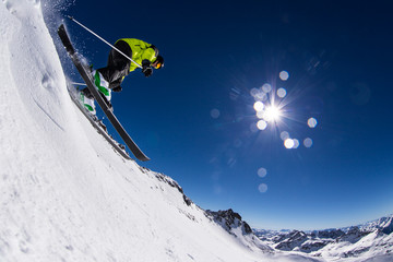 Alpine skier on piste, skiing downhill