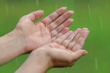 Hands under a rain