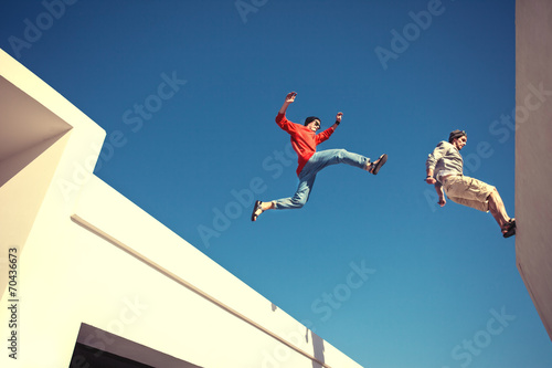 two brave men jumping over the roof, and little motion blur - 70436673