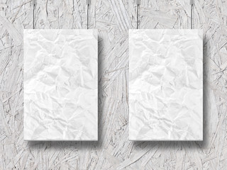 two hanging crumpled lists of paper and wooden background