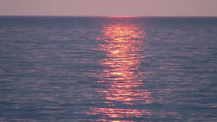 Pink sea sunset with a solar glitter path on the waves.