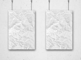 two hanging crumpled lists of paper and wall background