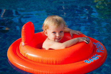 baby swimming in the orange float