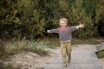 Young boy running with open arms. Oudoor portrait