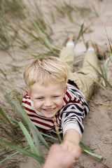 cheerful boy playing on the beach