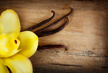 Vanilla Pods and Flower over Wooden Background