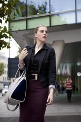 Woman walking on the sidewalk with handbag