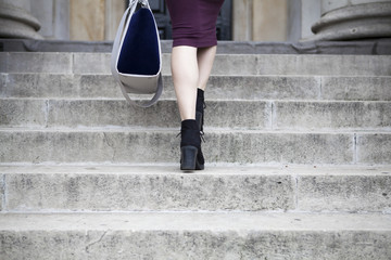 Feet and legs of woman walking up steps