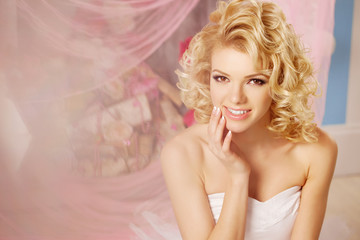 Cute woman looks like a doll in a sweet interior. Young pretty s