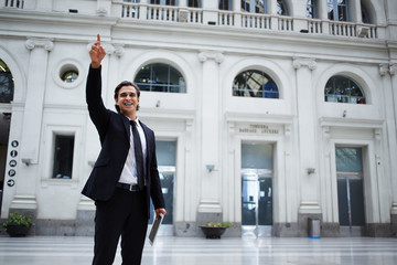 Smiling businessman waving hello to someone on train statio