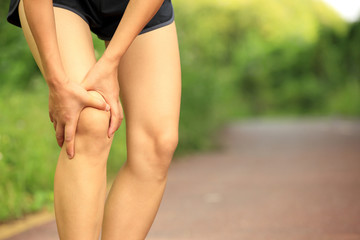 woman runner hold her sports injured knee