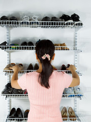 Woman selecting footwear from the shoe rack mounted on wall