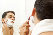 Young man shaving his beard with razor at the bathroom