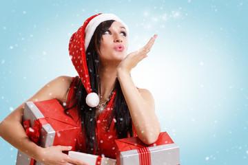 Frau mit Geschenken pustet Schnee in die Luft