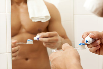 Close-up of a man squeezing toothpaste on the brush at the bathr