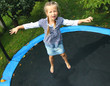 Happy girl playing on a garden trampoline.